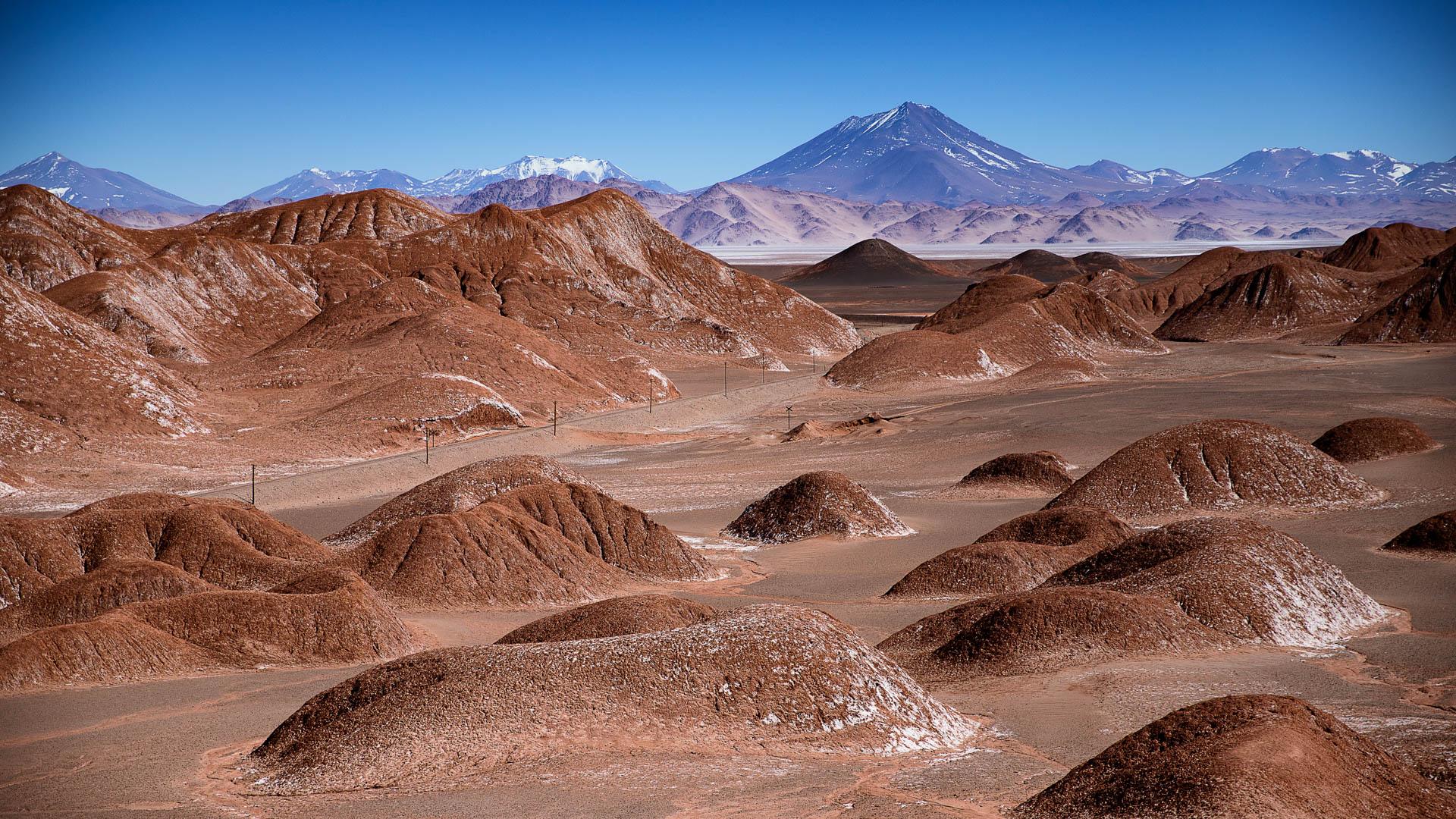Los montículos de arenisca roja que rodean al pueblo de Tolar Grande. Al fondo, volcanes cordilleranos.