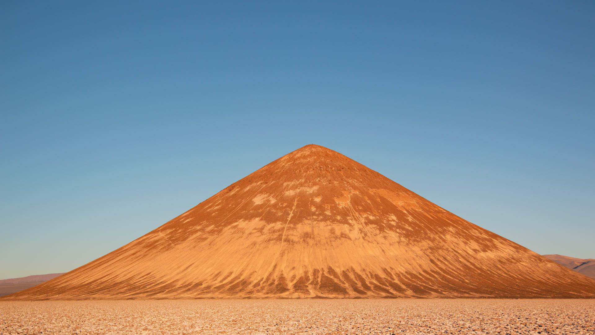 El cono de Arita teñido de naranja por las luces del atardecer. Lo enmarca el salar de Arizaro.